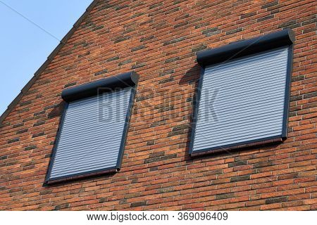 Rolling Shutters Brick House Windows Protection. Brick House With Metal Roller Shutters On The Windo