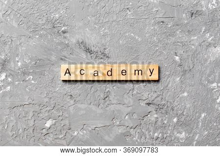 Academy Word Written On Wood Block. Academy Text On Cement Table For Your Desing, Concept