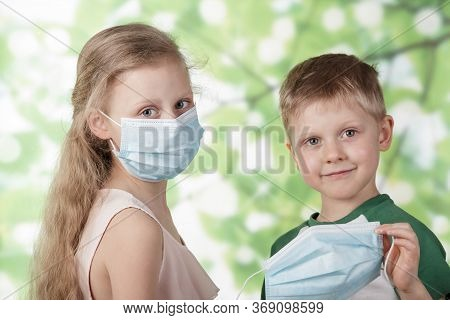 Boy And Girl Take Off Medical Mask And Go Play In The Garden, After Coronavirus Quarantine