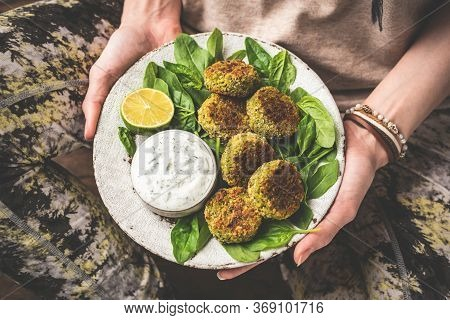 Girl Holding Plate Of Vegetarian Falafel With Sauce On Plate. Healthy Vegetarian Food Chickpea Spina