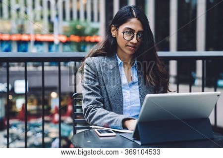 Ethnic Female Working With Papers And Tablet On Urban Backgraund