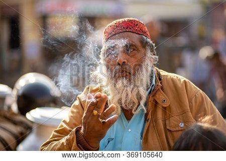 Jaisalmer, India - December 7, 2019: Portrait Of An Elderly Rajasthani Man Blowing Cigarette Smoke.
