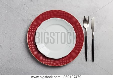 Minimal Table Setting With Red And White Dishes, Fork And Knife On Gray Concrete Background