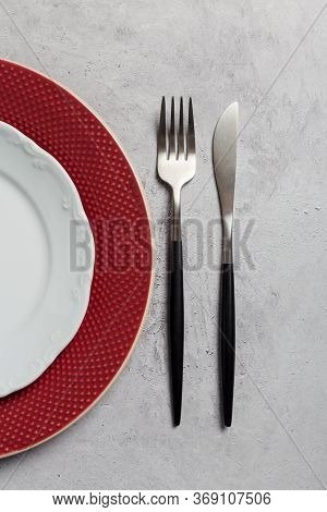 Close Up Table Set With Silverware On Gray Concrete. White And Red Dishes, Fork And Knife On Gray St