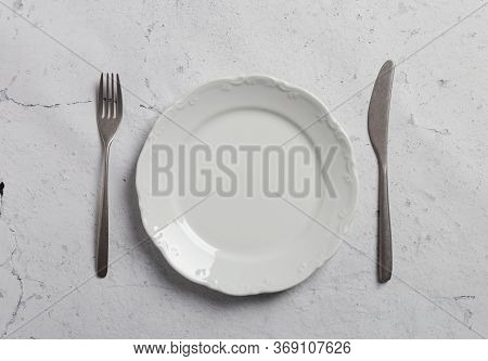 Modern Minimal Table Setting On Gray Concrete Background. Fork, Knife And Empty Plate On Stone Backg