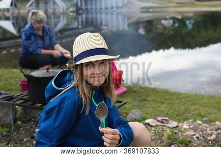 Young Teenager Girl On Riverbank Awaits Dinner With Spoon In Her Hand. Teenage Summer Vacations, Sch