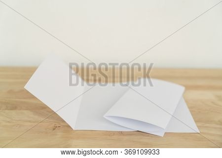 A4 tri-fold brochure blank white template for mock up and presentation design on wooden surface.