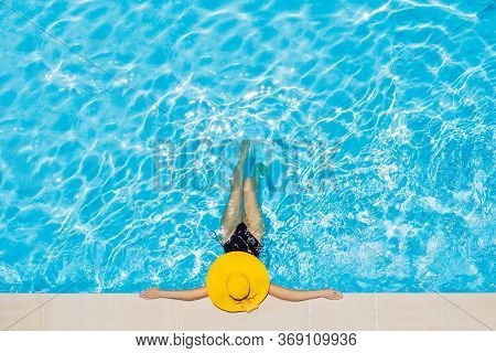 Woman Sitting In A Swimming Pool In A Large Yellow Sunhat