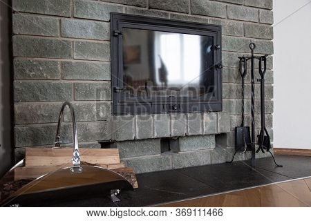 Gray Brick Wall Fireplace With Traces Of Black Soot. Cast-iron Fireplace Accessories And Firewood In