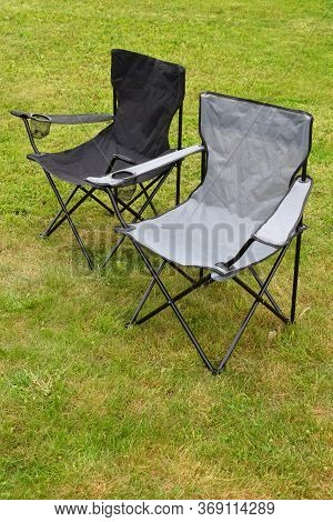 Two Grey And Black Empty Folding Camping Chairs In Green Lawn Grass Outdoors In Sunny Summer Day. Ca