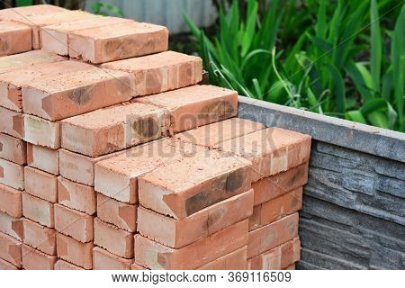 A Pile Of Red Bricks Are Neatly Piled Together On The Construction Site To Build A Brick Wall Of The