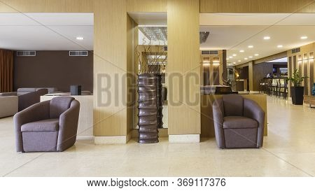 Brown Armchairs And Decor In Lobby Of Modern Hotel