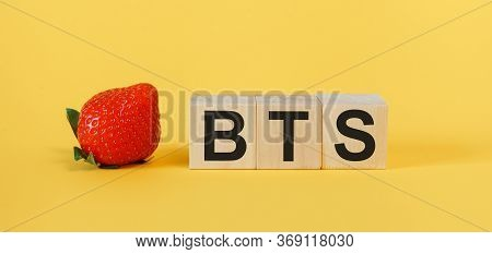 Bts Concept With Wooden Cubes. The Word Bts On A Yellow Background