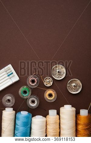 Sewing Tools On The Dark Brown Background With The Copy Space For Your Text