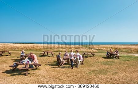 Scaborough, Uk - Sep 2, 2018: People Relaxing In A Yellow Meadow By The Sea In Sunny Day At Scaborou