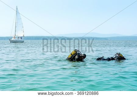 Two Industrial Divers With Scuba Gear Come Out Of The Water On The Shore Of The Lake, Copy Space. Ch