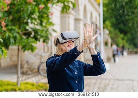 Blond Mature Woman Having Fun, Wearing Virtual Reality Goggles At Spring Time Outdoor. Close Up Port