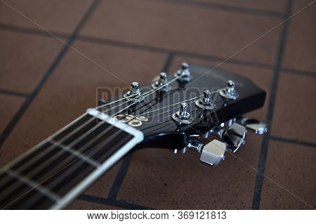 Headstock And Tuners Of Beautiful Black Acoustic Guitar Lying On The Brick Floor Closeup. Concept Of