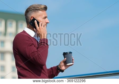 Using Communication Technologies. Handsome Guy Talk On Phone Drinking Coffee Outdoors. Mobile Commun