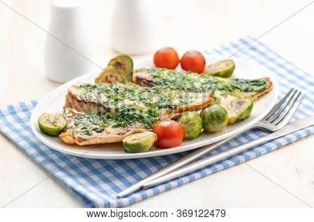 Baked White Fish Fillet With Vegetable Garnish And Butter And Lemon. Large Portion On A White Plate