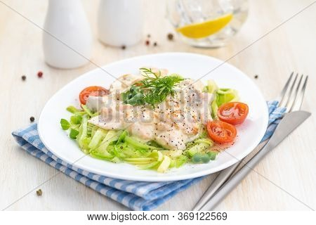 Salmon Slices In Creamy Sauces And Zucchini. Ketogenic Food. A Large Serving On A White Plate Is Rea
