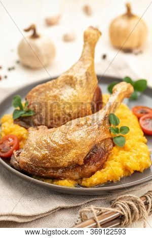 Roasted Duck Leg With Pumpkin Puree And Fresh Herbs. Large Portion On A Plate With A Napkin On A Woo