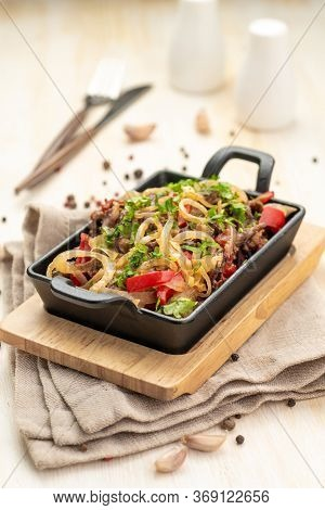 Roast Meat With Vegetables In A Cast Iron Skillet On A Wooden Background And A Linen Napkin. Traditi