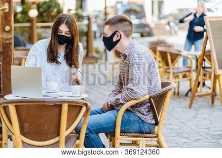 Waiter With Protective Medical Mask And Gloves Serving Guest With Coffee At An Outdoor Bar Caf Or Re