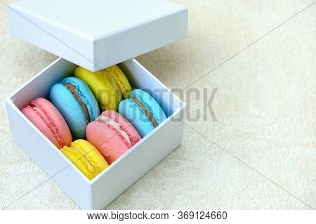 White Gift Box With Colorful French Sweet Cakes Macaroons. For Cafe Or Bakery Advertising With Copy