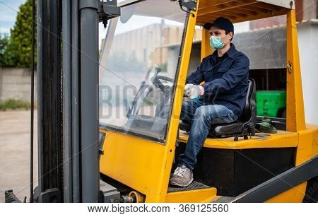 Worker using a forklift, driver at work in an industrial factory