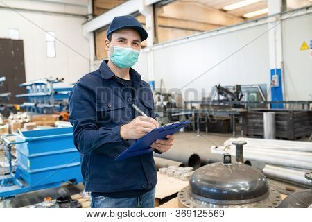 Industrial worker writing on a document in a factory