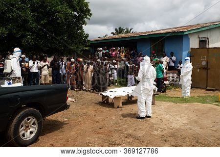 Lunsar, Sierra Leone, July 8, 2015: Burial Team And Family Praying Before Taking The Body Away. Ebol