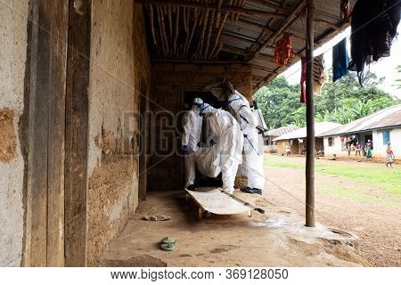 Lunsar, Sierra Leone, June 24, 2015: The Burial Team Takes A Dead Person From The Interior Of A Hous