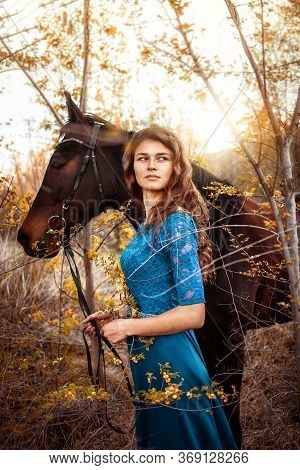 Beautiful Girl In A Blue Dress Hugs A Horse. Fairytale Photography, Artistic, Magical. Girl And Hors