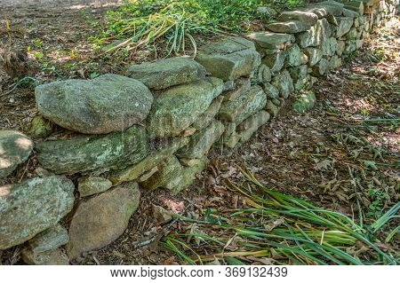 Angle View Of A Dry Stacked Rustic Stone And Rock Wall With Lichens And Moss Growing On The Surface