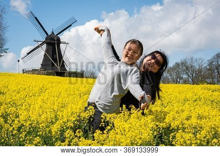 Mother And Daughter Dance In A Yellow Rapeseed Field With A Windmill In The Background To Celebrate