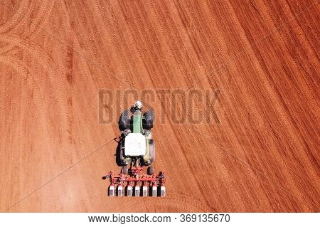 Farmer Seeding, Sowing Crops At Field With Tractor.sowing Is The Process Of Planting Seeds In The Gr