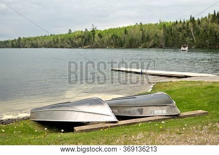 Overturned Rowboats Near A Dock On The Shore Of A Beautiful Minnesota Lake On A Calm And Cloudy Summ
