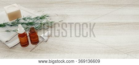 Rosemary Essential Oil And Fresh Twig On Wooden Background. 3d Rendering