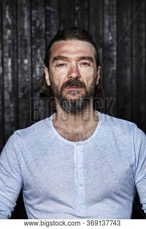 Bearded Man Has A Serious Face Expression On His Face. Portrait Of A Handsome Mature Man In His 40's