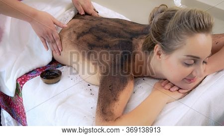 Relaxed Woman Lying On Spa Bed For Body Scrubbing.