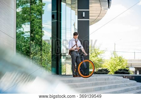 Busy white collar worker in formalwear scrolling in smartphone while standing by staircase and leaving office center after work