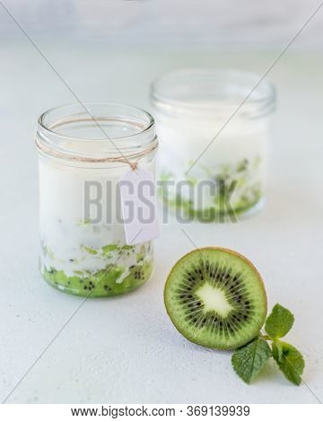 Two Jar With Smoothie From Kiwi And Milk And Mint At White Background. Concept Of Summer Food And Be
