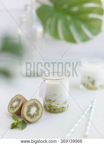 Smoothie From Kiwi And Milk In Jar At Light Background With Tropical Leaves Behind