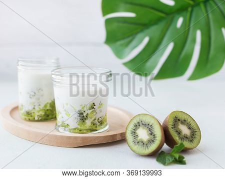 Smoothie From Kiwi And Milk In Jar At Light Background With Tropical Leaves Behind. Concept Of Healt