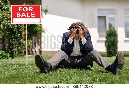 Depressed Real Estate Agent Sitting On Grass In Front Of House For Sale, Outside