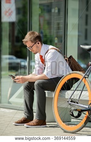 Young agent in formalwear scrolling in smartphone while sitting on bench by business center and waiting for client in urban environment