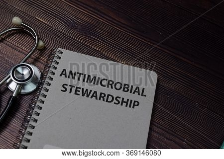 Book About (ams) Antimicrobial Stewardship Isolated On Wooden Table.