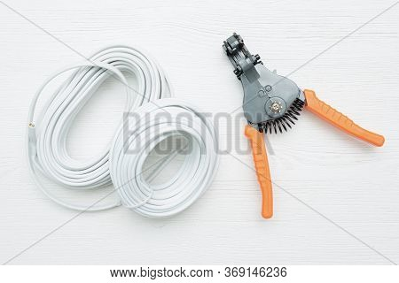 Cable Stripper And Electrical Wiring On The White Workbench Background.