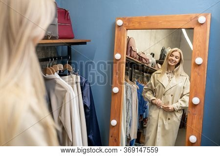 Happy young blond woman trying on new elegant beige coat in front of mirror in changing room while choosing new clothes for spring